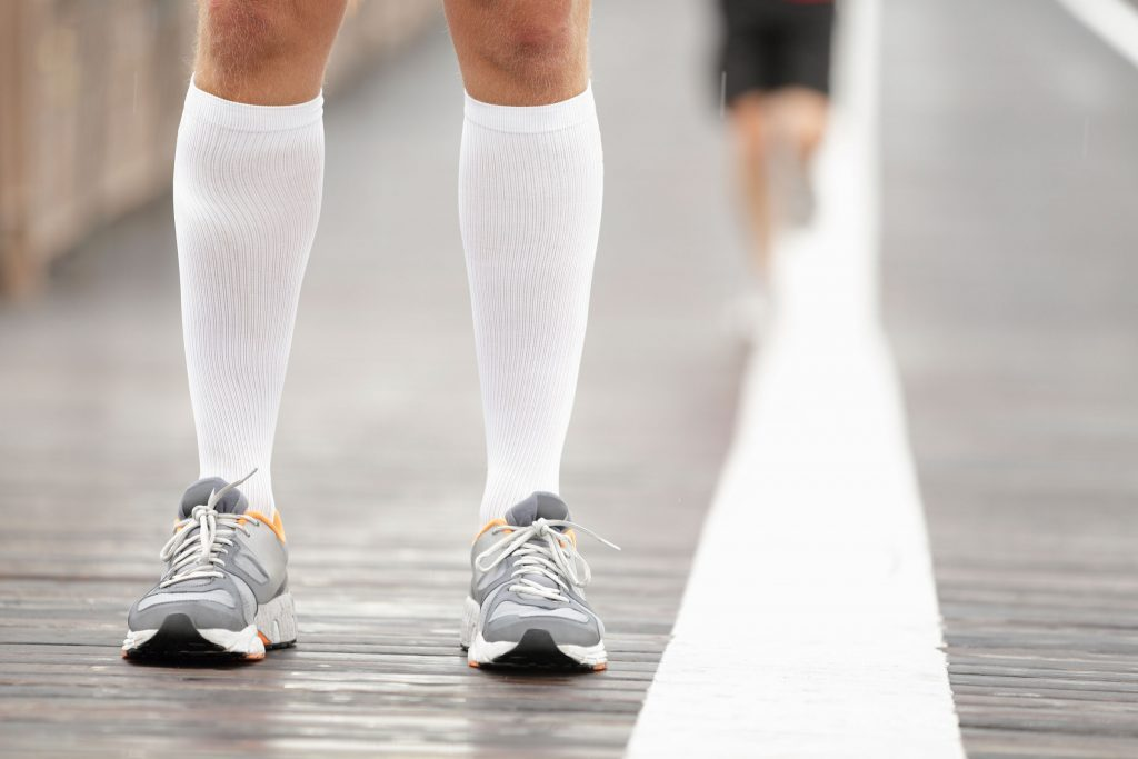 person wearing compression socks and sneakers
