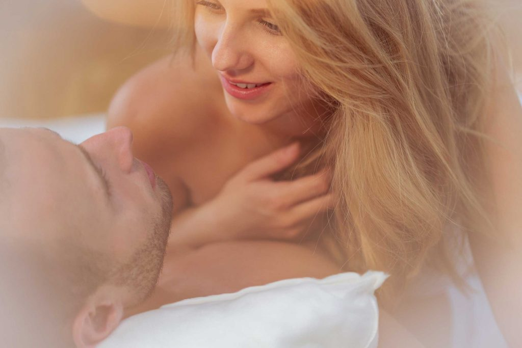 man on his back in bed with woman looking into his eyes