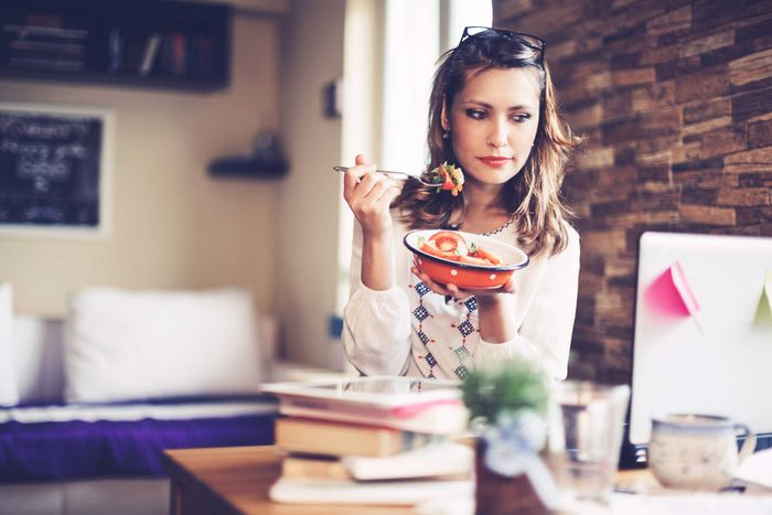 woman eating healthy food at her desk