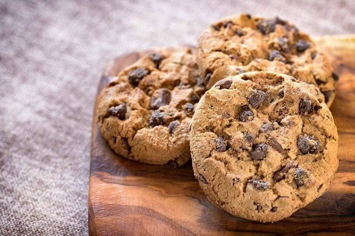 Chocolate chip cookies arranged on a wooden cutting board.
