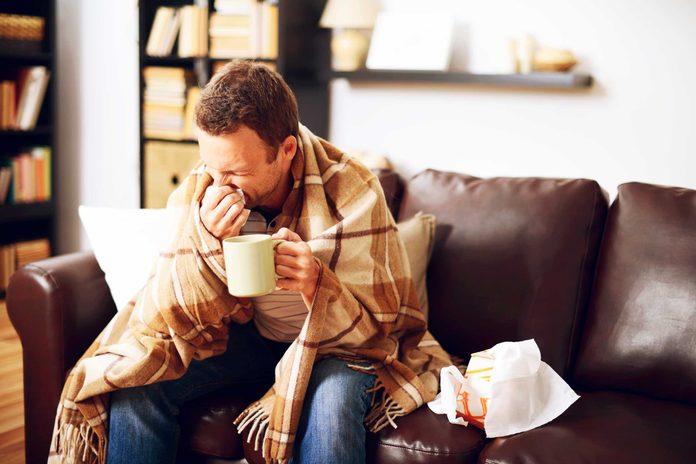 man wrapped in a blanket on a couch, sneezing