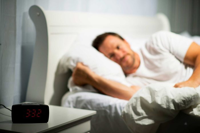 awake man lying on bed looking at a bedside table clock