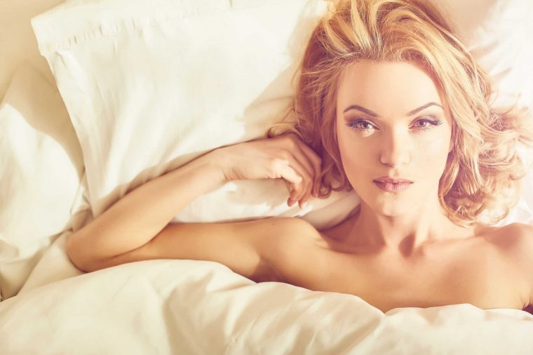 woman in bed, confident look as she stares into the camera