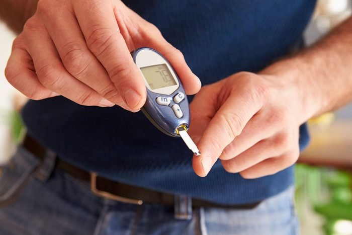 man testing his finger with glucometer