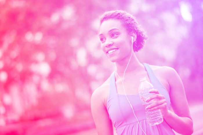 black woman with earbuds outdoors