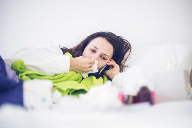 sick woman in bed with tissue