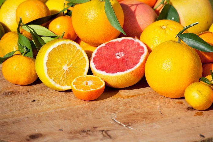 red and yellow grapefruit halves amongst a pile of whole grapefruits