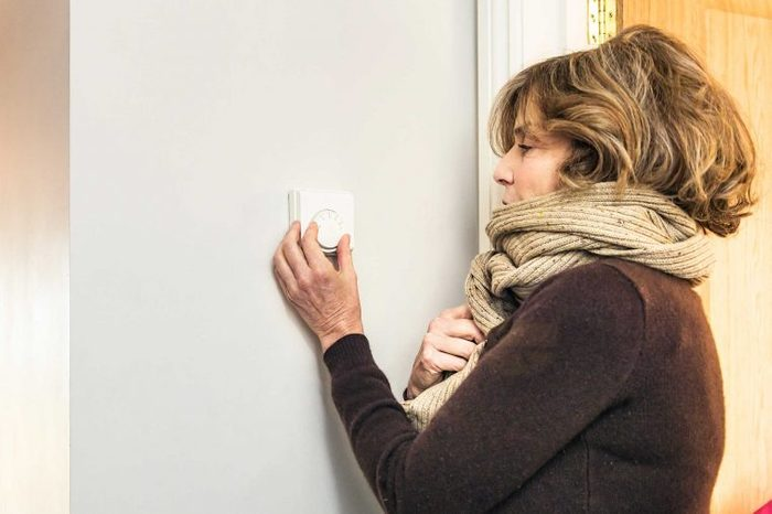 Woman in a scarf turning up the thermostat at her house.