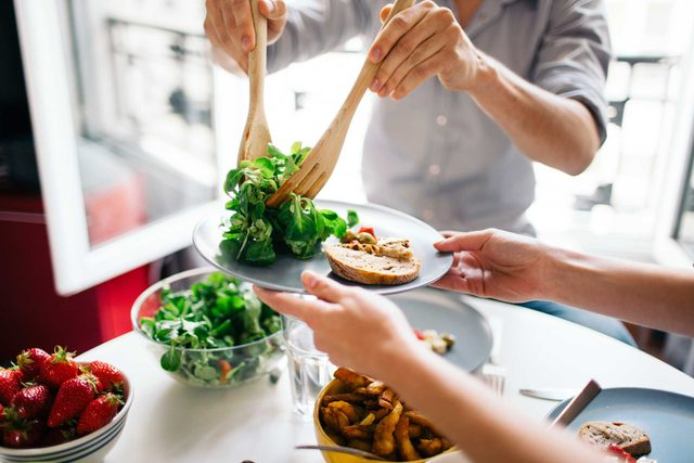 person serving salad onto another person's plate
