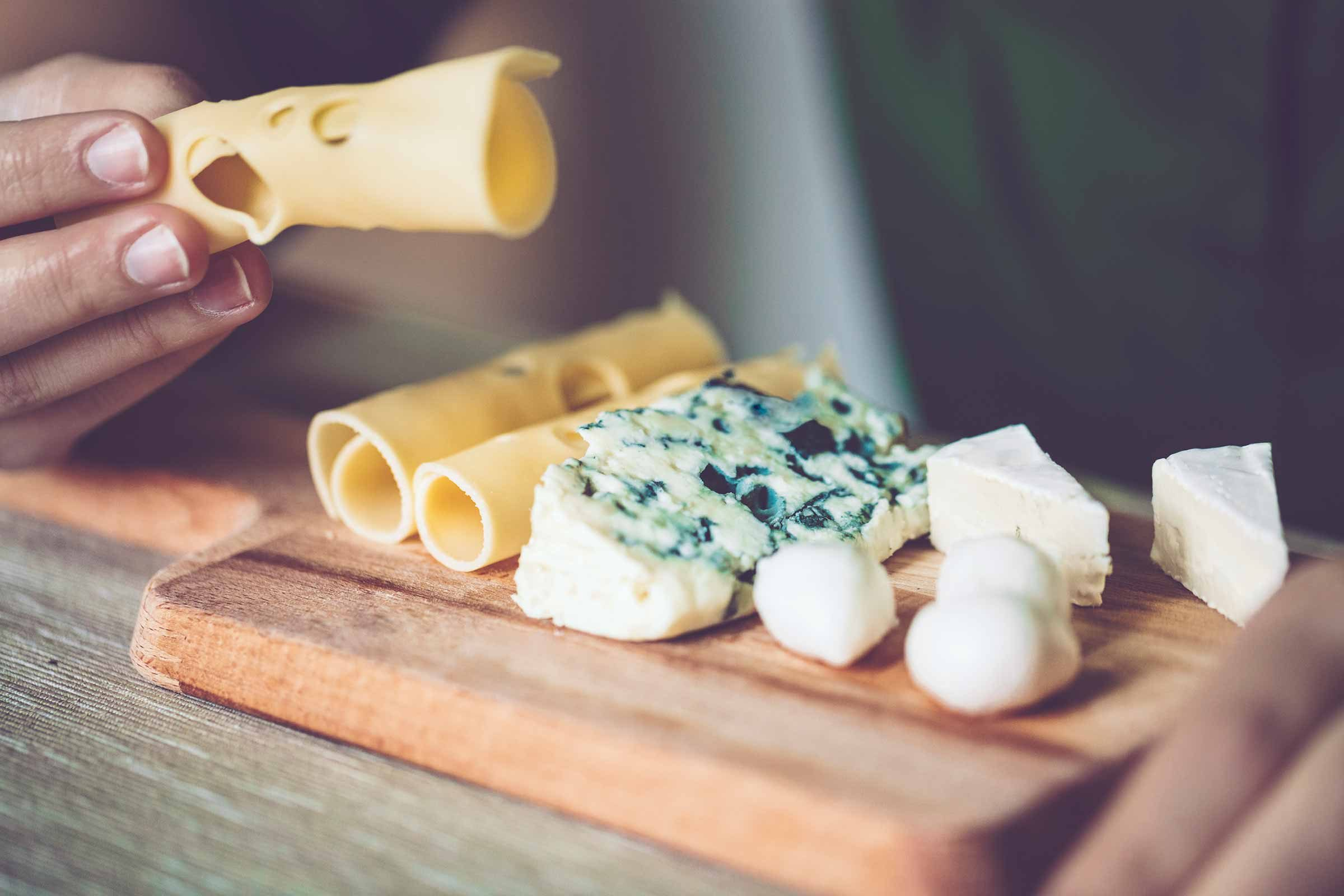 Swiss cheese, blue cheese, brie cheese, and mozzarella balls arranged on a wooden platter, with a man sampling the Swiss cheese.