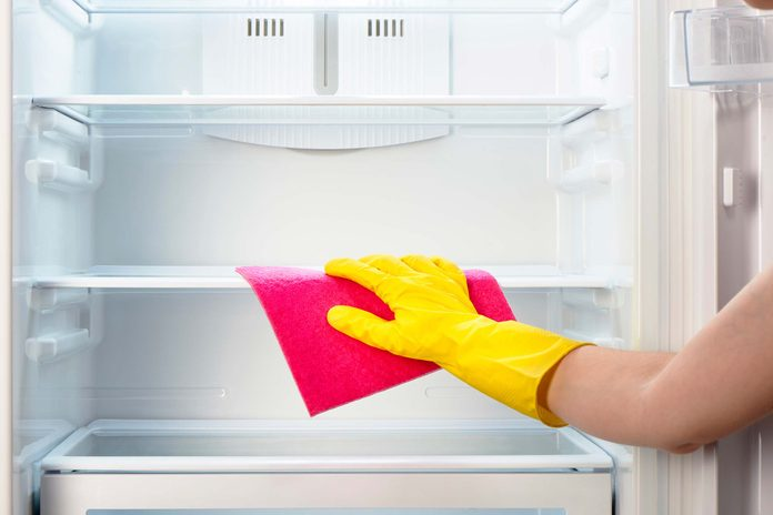 Cleaning shelves inside a refrigerator.