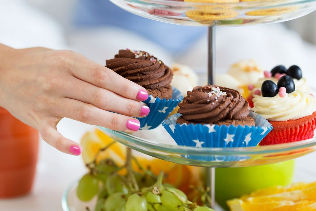 woman's hand grabbing a cupcake from a stacked tray