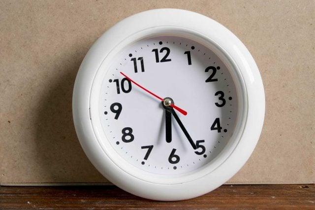 White clock resting on a hardwood floor.