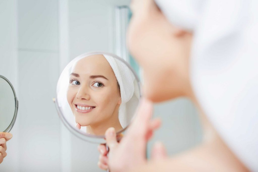 woman with hair wrapped in towel looking into a handheld mirror