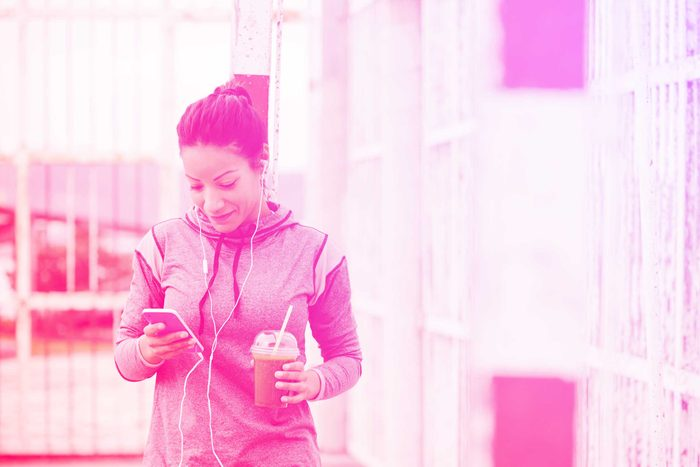 woman in exercise gear checking her smartphone outdoors