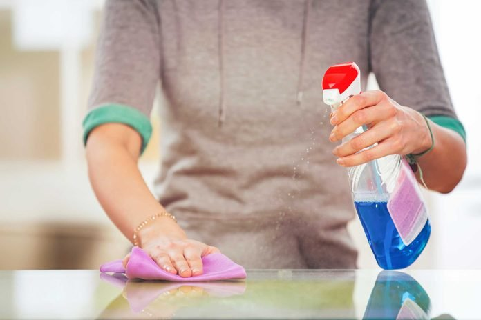 woman cleaning a countertop with cloth and spray bottle