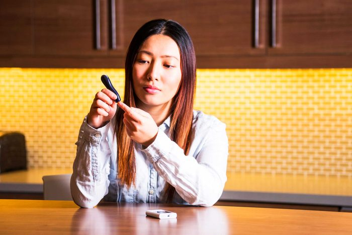 woman with glucometer testing tip of finger