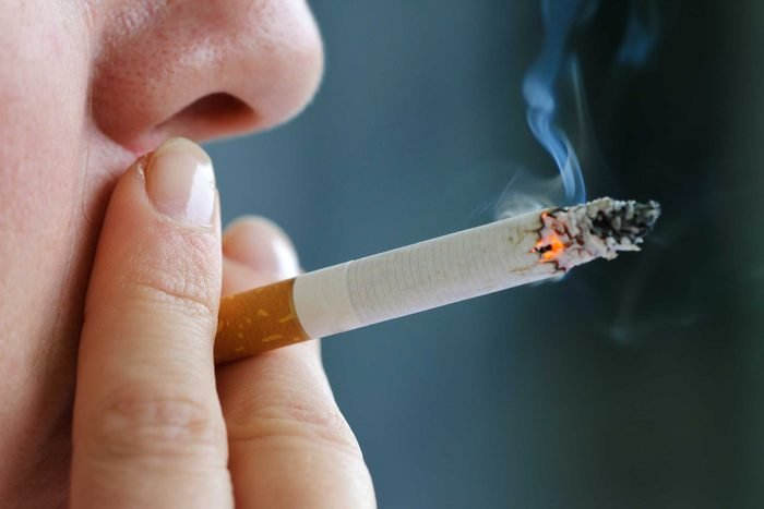 close up of person smoking a cigarette
