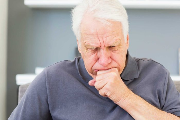 gray-haired man coughing