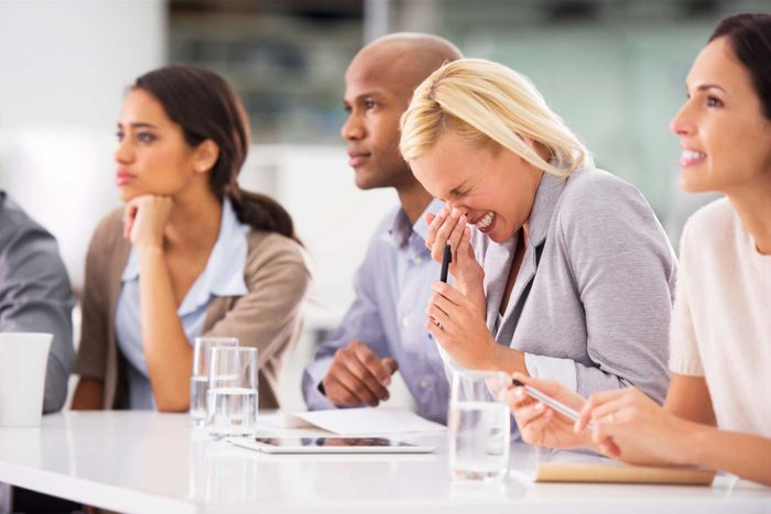 people at a table with one woman sneezing