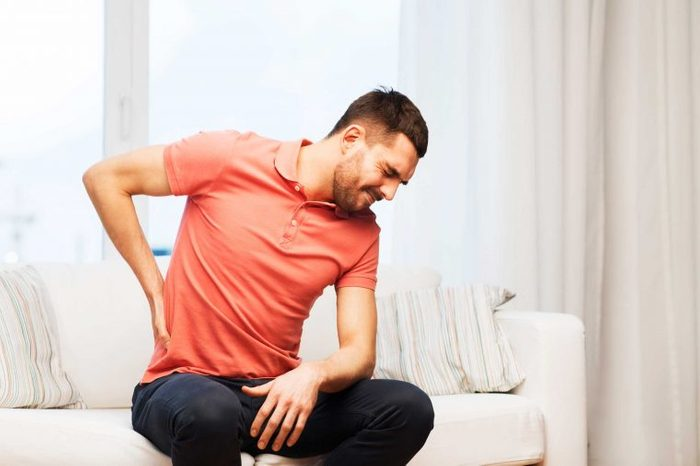 Man sitting on the couch holding his back as if having a backache.