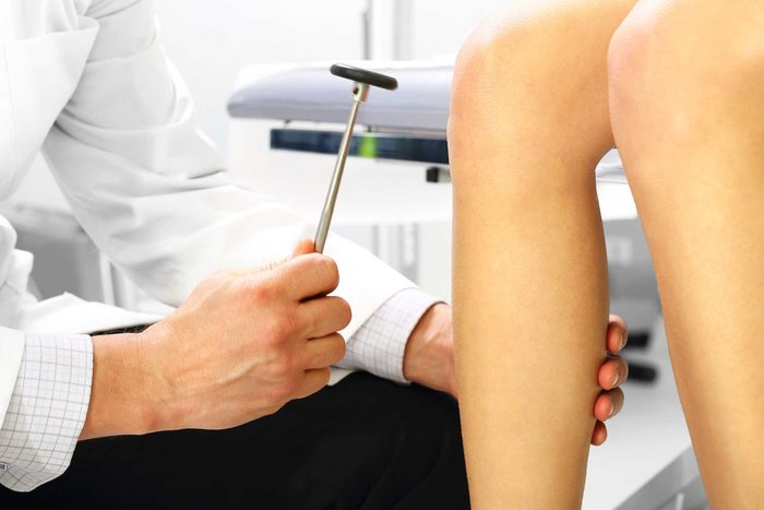 close-up of doctor testing knee reflex with rubber hammer