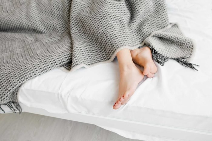 A person's feet poking out from underneath a gray blanket.
