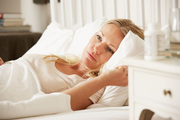 awake woman lying in a bed