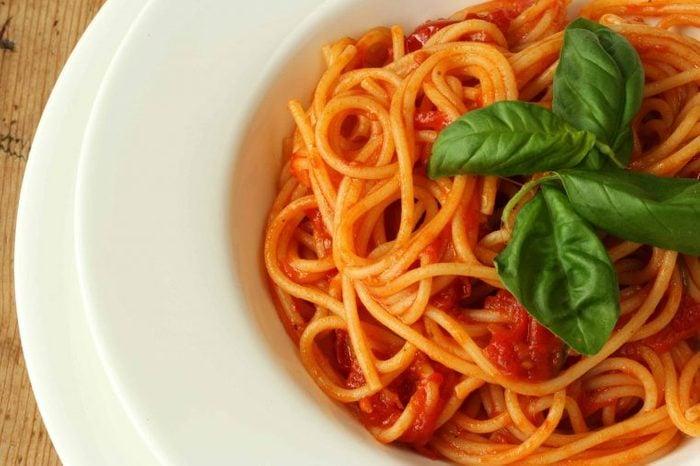 White bowl of tomato pasta with basil.