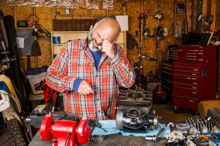 Man in his garage workshop rubbing his eye.
