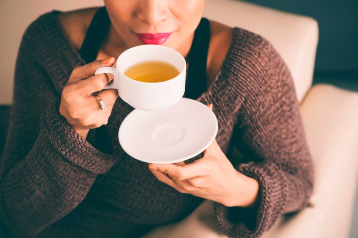 woman sitting on couch and sipping tea