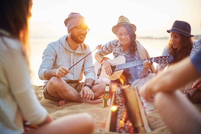 Friends by a campfire on a beach