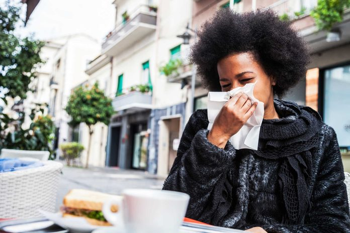 African American woman sneezing into a tissue