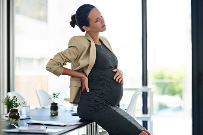 pregnant woman sitting on desk in office