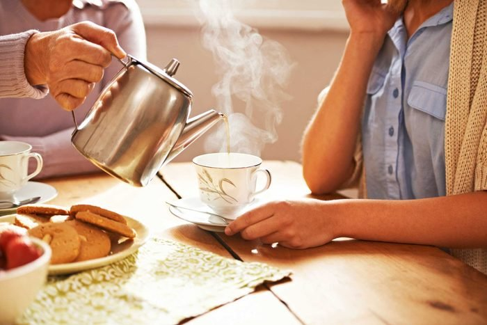woman pouring another woman a cup of tea with teapot