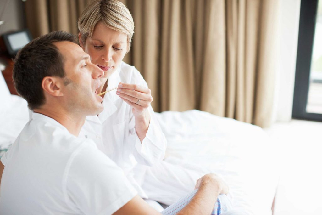 woman checking a man's temperature with a thermometer