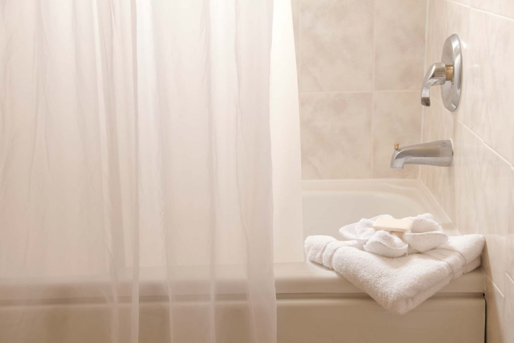 Bathtub with shower curtain.