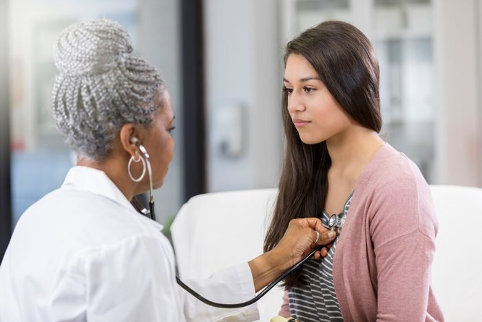 doctor listening to young girl's heart with stethoscope