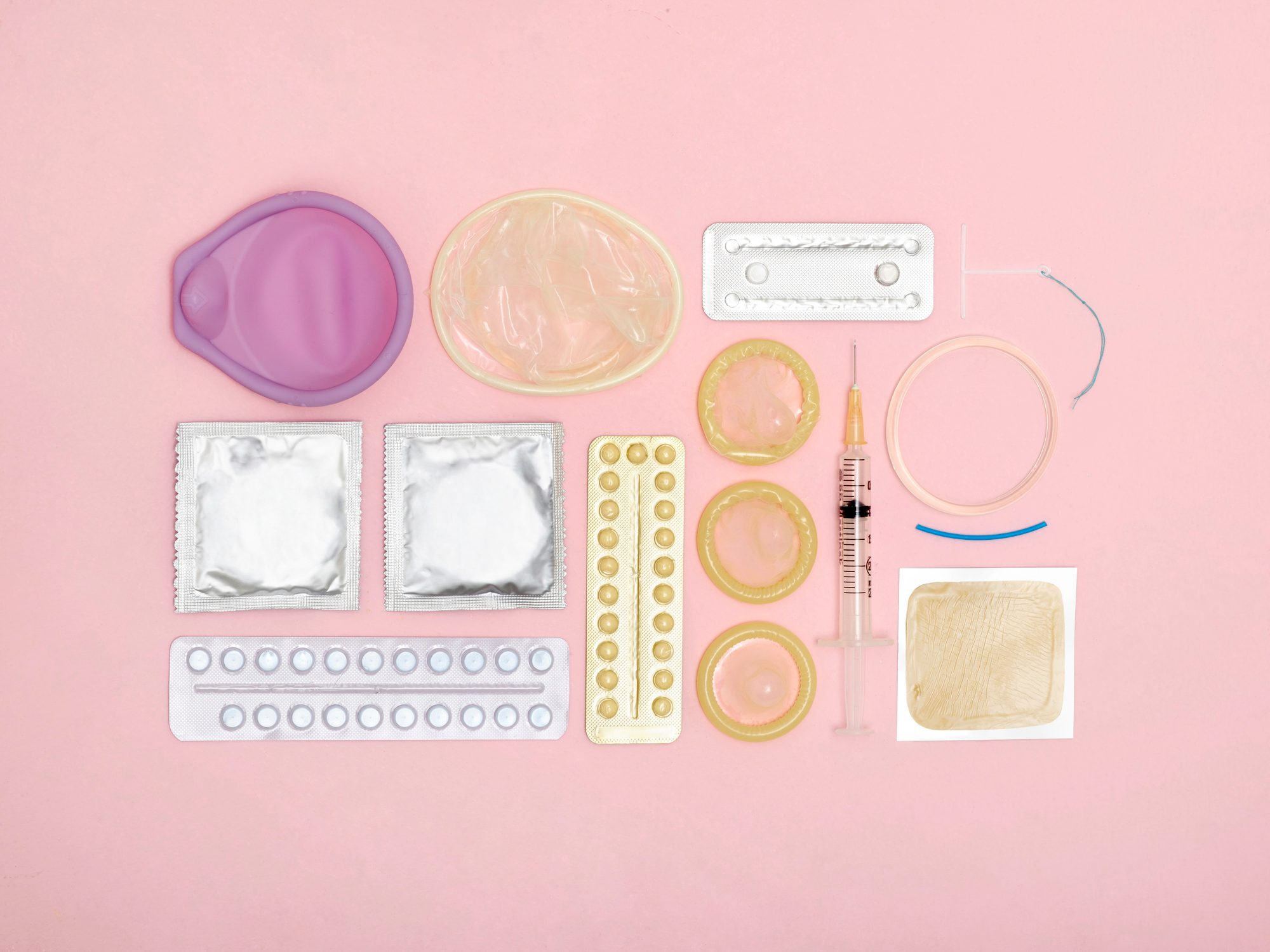 variety of birth control methods on pink background