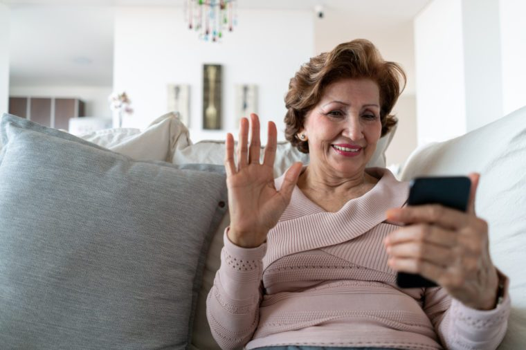 senior woman sitting on couch at home on a video call with family and friends