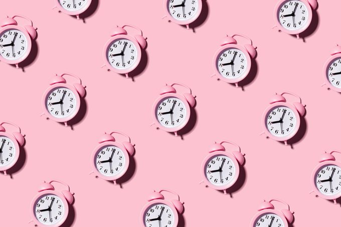 pink alarm clocks on pink background