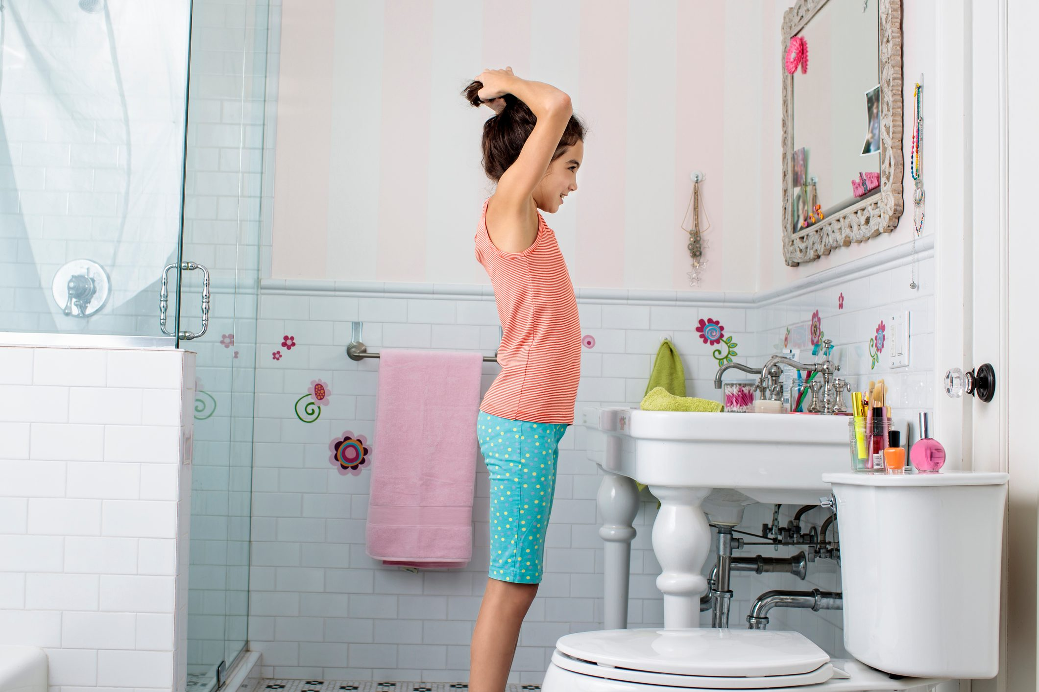 young girl fixing her hair in the bathroom mirror