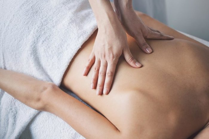 woman's hands massaging another woman's back