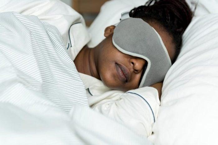 woman sleeping in bed with sleep mask on