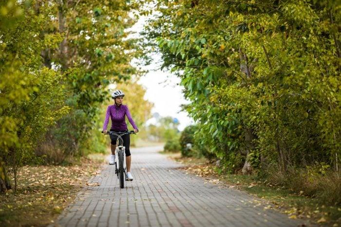 woman on a bike ride through neighborhood nature trail