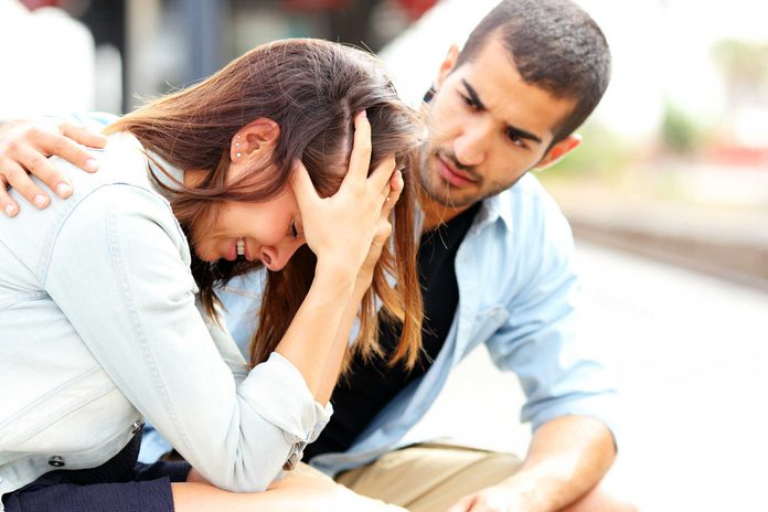 man with arm around upset woman