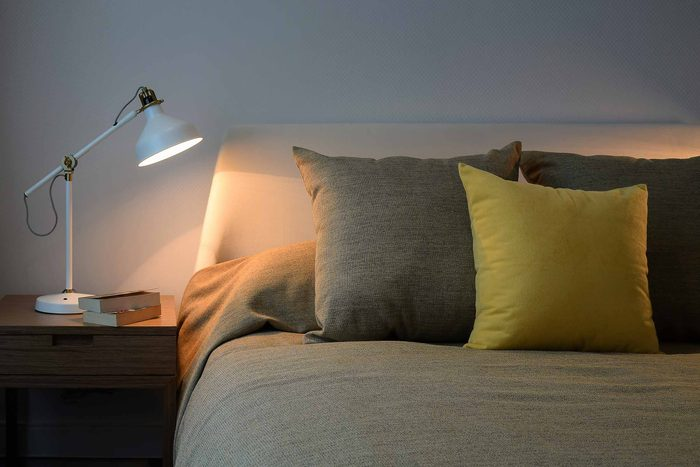 Bedside lamp next to an empty bed