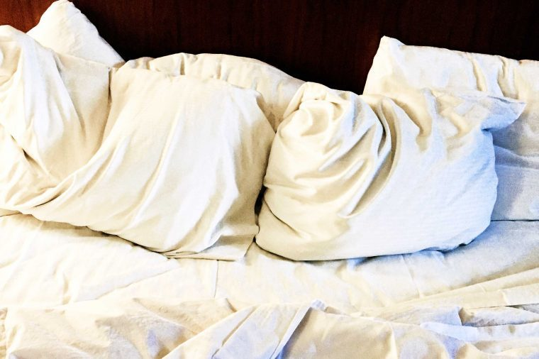 Unmade bed with multiple white pillows on it.