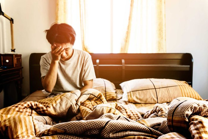 man sitting in bed, head in hand