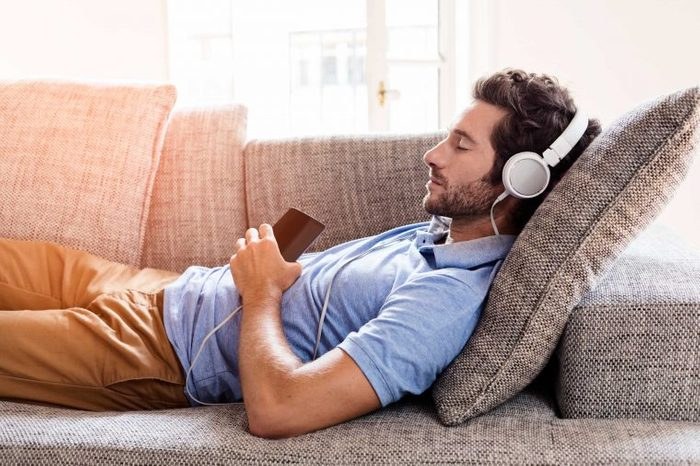 Man closing his eyes, reclining on the couch while wearing headphones and listening to music.